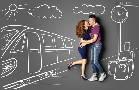 Happy valentines love story concept of a romantic couple against chalk drawings background of a railway station. Male meeting his girlfriend at the station and kissing her under a street clock.