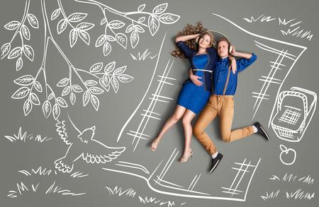 幸せなバレンタインのヘッドフォンの共有とチョーク図面背景音楽を聴いてピクニックにロマンチックなカップルの物語のコンセプトが大好きです 写真素材