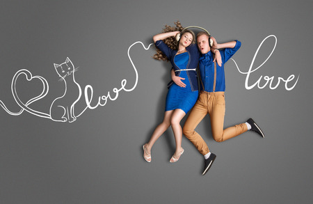 lyrics: Happy valentines love story concept of a romantic couple sharing headphones and listening to the music about love against chalk drawings background of lyrics. Stock Photo