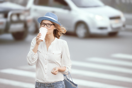 Happy young fashionable student drinking hot take away coffee and crossing a road against urban background.