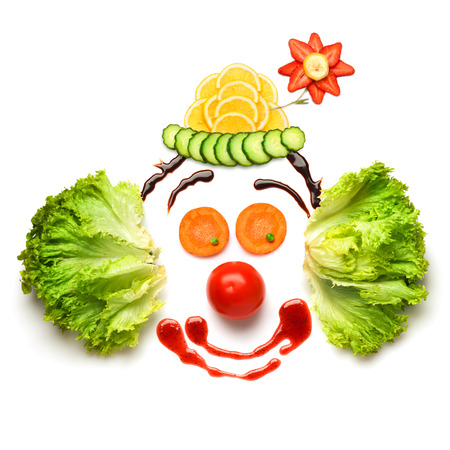 A nice and funny edible clown, made of strawberries, lemons, salad and so on.
