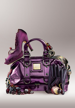 designer bag: Violet shoe on a purse with jewelry and gloves.