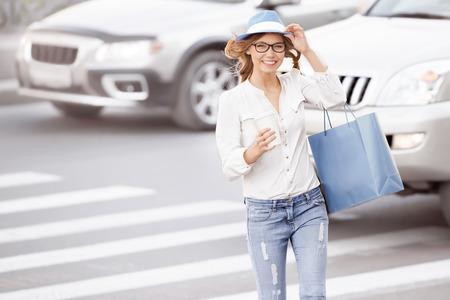 paso de peatones: Joven estudiante femenina feliz de cruzar la calle con una taza de café-a-go y propinas sombrero contra el fondo urbano de la ciudad.