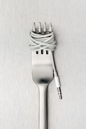 metal music: A shining fork with noodle made of cable with music jack plug in metal background.