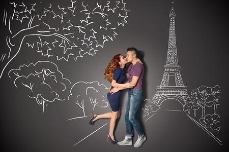 parejas romanticas: Happy valentines encanta concepto historia de una pareja romántica en París besándose bajo la Torre Eiffel contra dibujos de tiza de fondo. Foto de archivo