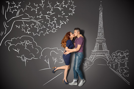 story: Happy valentines love story concept of a romantic couple in Paris kissing under the Eiffel Tower against chalk drawings background.