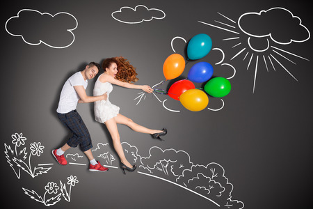 Happy valentines love story concept of a romantic couple holding balloons blowing with the wind against chalk drawings background. Archivio Fotografico