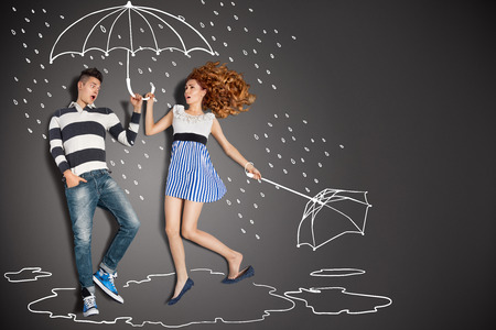 Happy valentines love story concept of a romantic couple in the rain against chalk drawings background.