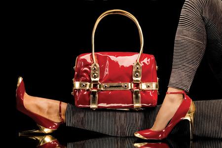 Un gros plan d'un sac à main rouge chic, avec des jambes féminines sexy portant des élégantes chaussures rouges. Banque d'images - 40338438