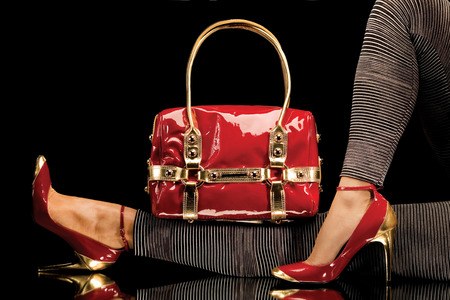 tacones rojos: Un primer plano de un bolso rojo elegante junto con piernas de mujer sexy con zapatos rojos elegantes. Foto de archivo