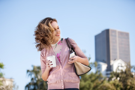 to go cup: A beautiful woman checking email via mobile phone in a city park.
