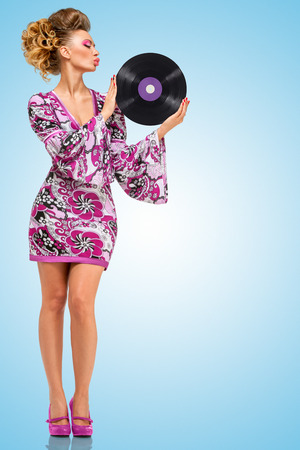 Colorful photo of a clubbing fashionable hippie homemaker sending a kiss to a retro vinyl record in her hands on blue background.