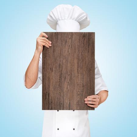 Chef du restaurant se cachant derrière une planche à découper en bois pour un menu déjeuner d'affaires avec des prix. Banque d'images - 40338644