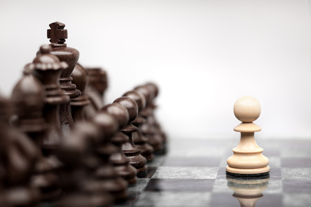 One pawn staying against full set of chess pieces. Stock Photo - 40402359