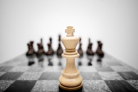 chess: La foto significativa de rey del ajedrez de permanencia ante el conjunto de otras piezas de color.