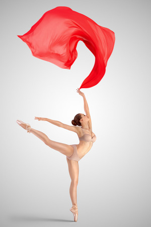 tiptoe: A graceful female classical ballet dancer on pointe shoes wearing beige underwear, standing on one leg in arabesque position and throwing red fabric on a neutral light studio background.