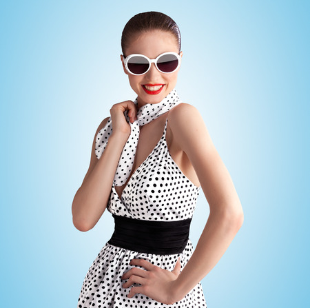 Creative vintage portrait of a beautiful pin-up girl wearing a fashionable retro dress in polka dots on blue background.