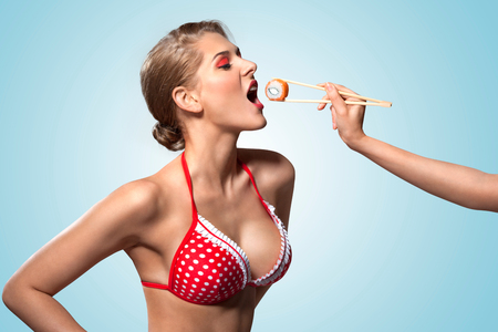 sexy party girl: A creative retro photo of a young pin-up girl in bikini eating sushi from chopsticks. Stock Photo