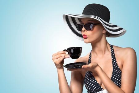 niña comiendo: Una foto de época creativa de una hermosa chica pin-up beber té y mostrando buenos modales en la mesa. Foto de archivo