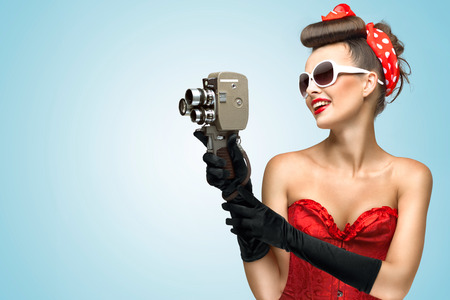 A photo of the pin-up girl in corset and gloves holding vintage 8mm camera. Imagens