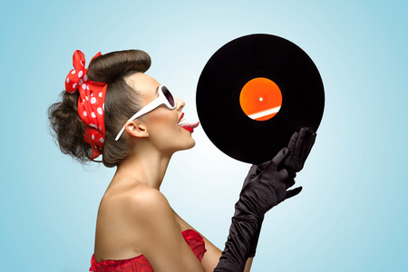 tongue: A photo of glamorous pin-up girl touching vinyl LP with tongue.