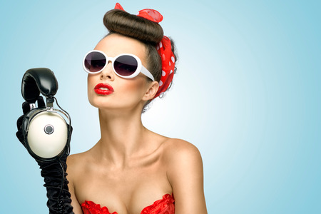 listening device: The retro photo of a cute pin-up girl in sunglasses with vintage music headphones. Stock Photo