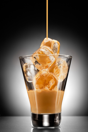 baileys: Irish creme liqueur pouring into a glass full of ice. Stock Photo