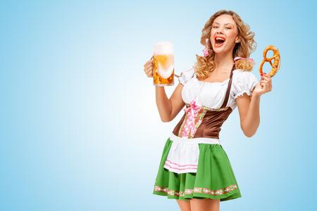 Young Oktoberfest waitress wearing a traditional Bavarian dress dirndl offering a pretzel and beer mug on blue background.