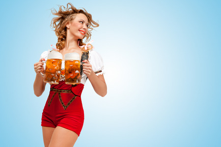 Young smiling Swiss woman wearing red jumper shorts with suspenders in a form of a traditional dirndl, holding two beer mugs and looking aside on blue background.