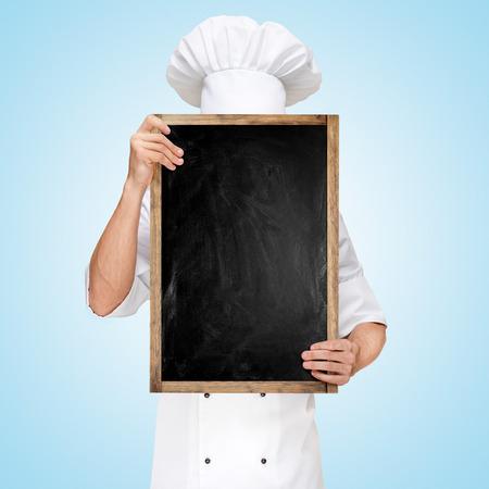 chef: Chef del restaurante escondido detrás de una pizarra en blanco para un menú de almuerzo de negocios con los precios. Foto de archivo