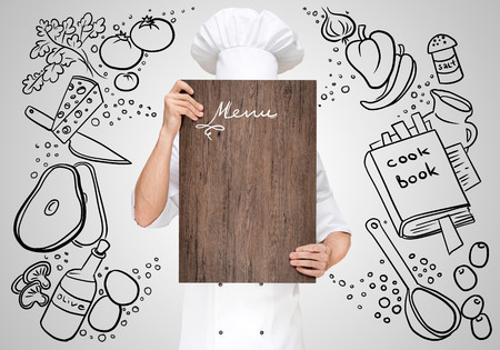 Restaurant chef on a sketchy background hiding behind a wooden chopping board for a business lunch menu with prices. Stock Photo