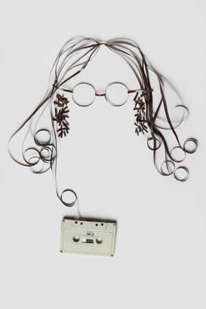 A beautiful image made of tape cassette with the tape forming a face of hair glasses on bright background.