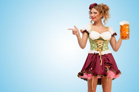 Oktoberfest camarera sexy joven que llevaba un tradicional dirndl vestido bávaros sosteniendo una jarra de cerveza, y que apuntan a un lado en el fondo azul.
