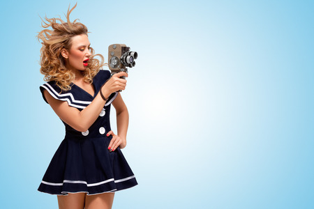 sailor girl: Retro photo of a glamorous pin-up sailor girl with an old vintage cinema 8 mm camera shooting a movie on blue background.