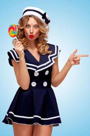 sailor girl: Creative photo of a playful pin-up sailor girl with a colorful lollipop, pointing aside with a finger on blue background. Stock Photo