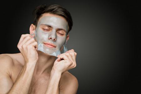 페이셜 마스크, 얼굴과 몸 피부 관리 퇴각을 벗겨 아름다운 젊은 남자의 초상화.