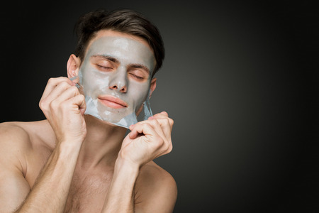 aging: Portrait of a beautiful young man peeling off a facial mask, face and body skin care retreat.
