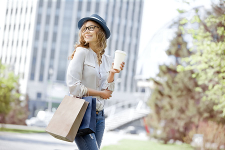 Happy young trendy woman drinking take away coffee and walking with shopping bags after shopping in an urban city.