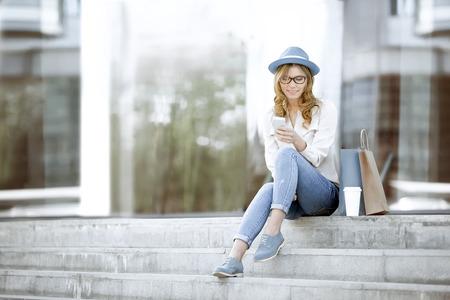 mujeres felices: Mujer joven feliz con una taza de caf� y de compras bolsas desechables que se sienta en las escaleras y el uso de su tel�fono inteligente para la comunicaci�n a trav�s de wi-fi a internet en un parque de verano.