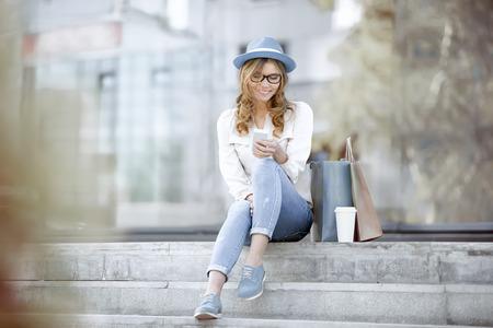 使い捨てのコーヒー カップとショッピング バッグ、階段の上に座ってと夏のパークで wi-fi インターネット経由の通信に彼女のスマート フォンを使 写真素材