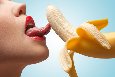 A face of a hot girl that is licking a half-peeled yellow banana.