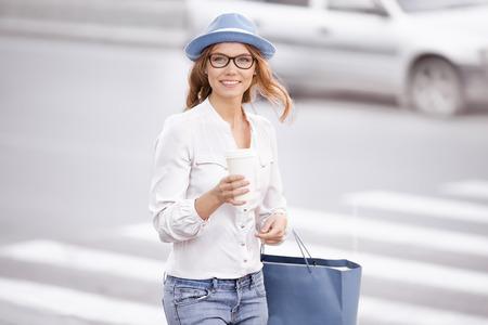 paso de peatones: Joven y bella mujer de pie en el paso de peatones con una taza de café-a-go, sonriendo feliz contra el fondo urbano de la ciudad.