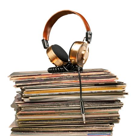黄金のヘッドフォンはビニール レコードのスタックの上に横たわる。