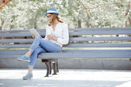 タブレットと使い捨てのコーヒー カップのベンチに座って、夏の公園で本を読んで幸せな若い学生。