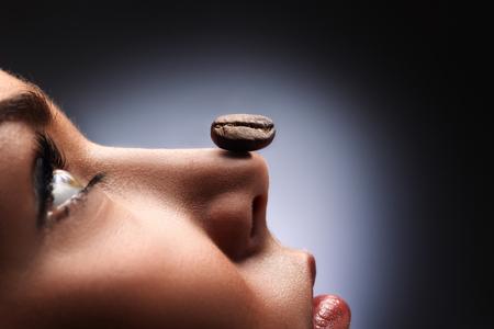 nariz: Un tostado del grano de café negro en la nariz de una hermosa muchacha que huele el café y relajante. Foto de archivo