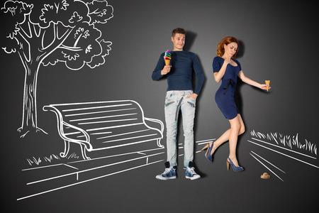 romantique: Happy valentines amour concept de l'histoire d'un couple romantique dans le parc de manger des glaces contre dessins � la craie fond. Banque d'images