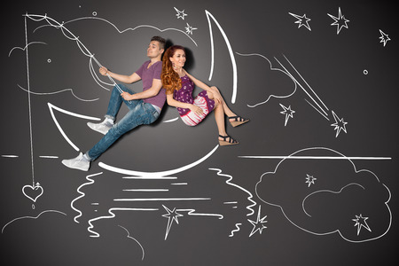 story: Happy valentines love story concept of a romantic couple fishing on a moon with a heart on a hook against chalk drawings background.