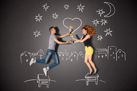 Happy valentines love story concept of a romantic couple standing on a stool and painting a heart in the night sky against chalk drawings background.