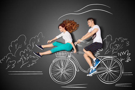 Happy valentines love story concept of a romantic couple against chalk drawings background. Male riding his girlfriend in a front bicycle basket.