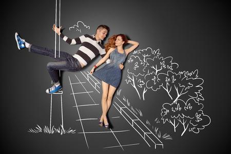 幸せなバレンタイン チョーク図面背景のロマンチックなカップルの物語のコンセプトが大好きです。男性ポールダンス街灯にガール フレンドと歩い 写真素材